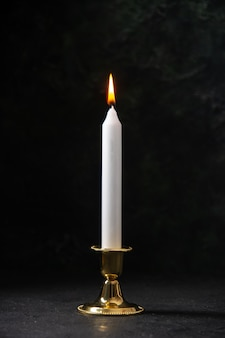 Front view of white candle in golden stand on black