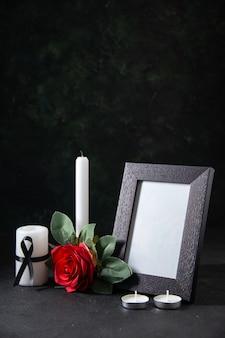 어두운 표면에 액자와 꽃이있는 전면보기 하얀 촛불