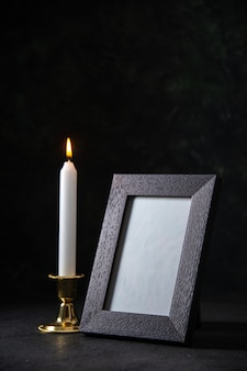 Vista frontale della candela bianca con cornice su sfondo scuro