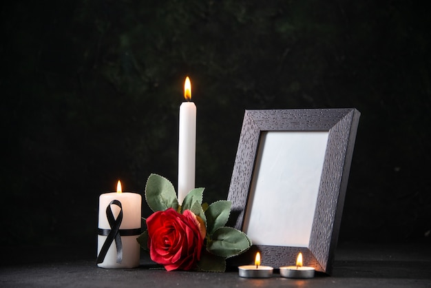Front view white candle with picture frame and flower on dark desk funeral evil death