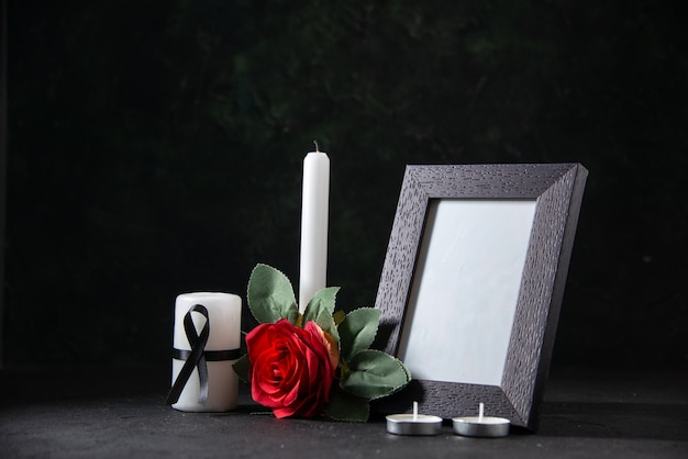Front view white candle with picture frame and flower on dark surface