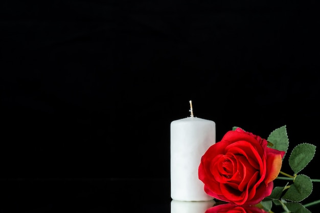 Front view of white candle with red rose on black