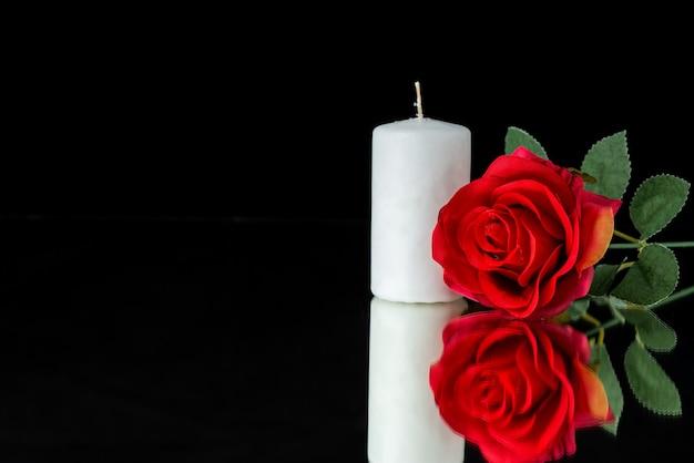 Vista frontale della candela bianca con rosa rossa su fondo nero
