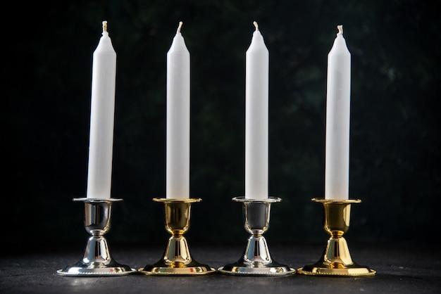 Vista frontale delle candele bianche in supporto dorato e argento su nero