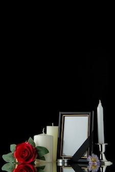 Vista frontale di candele bianche con cornice sulla parete nera