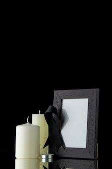 Front view of white candles with picture frame on black wall
