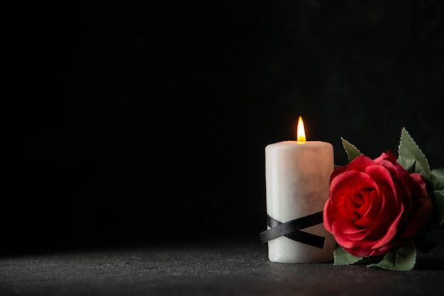 Front view of white candles with red flower on dark wall