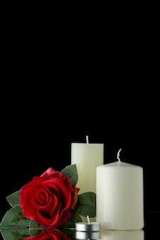 Vista frontale di candele bianche con fiori rossi su parete nera