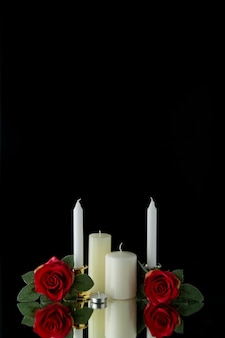 Front view of white candles with red flowers on black wall