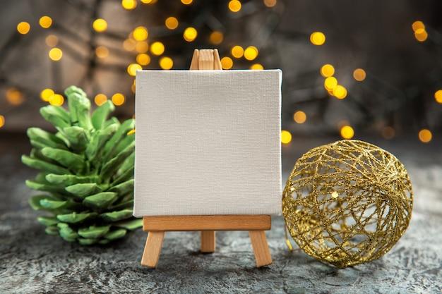 나무 이젤에 전면 보기 흰색 캔버스 크리스마스 조명 어둠에 크리스마스 장식품