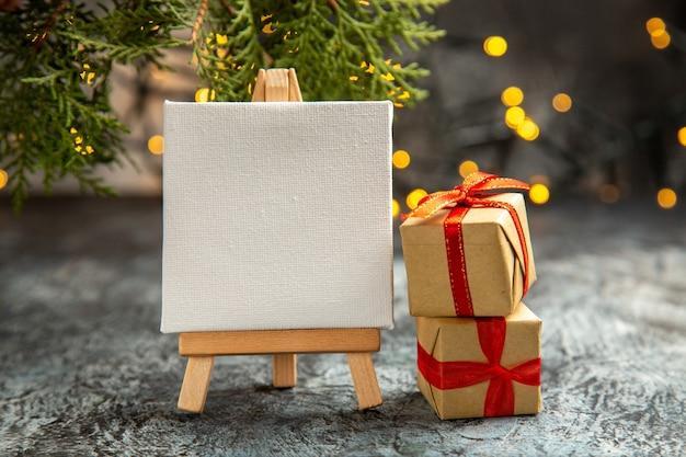 Vista frontale tela bianca su cavalletto in legno scatole regalo luci di natale su buio