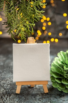 Front view white canvas on wood easel xmas lights pine branches on dark background