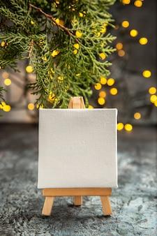Tela bianca vista frontale su cavalletto in legno luci natalizie rami di pino su oscurità
