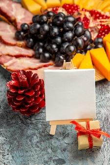 Vista frontale tela bianca su cavalletto in legno uva pezzi di formaggio fette di carne su piatto di legno dettagli di natale su buio