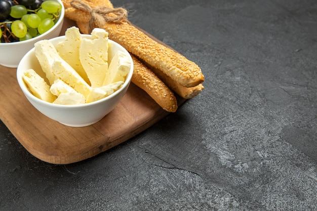 暗い背景にブドウとパンと正面図の白いチーズ食品ミルクパンフルーツ