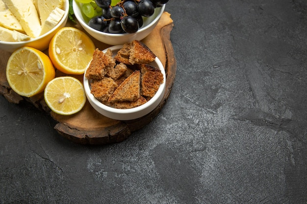 暗い背景にブドウとレモンのスライスと正面図の白いチーズ食品ミルクパンフルーツ