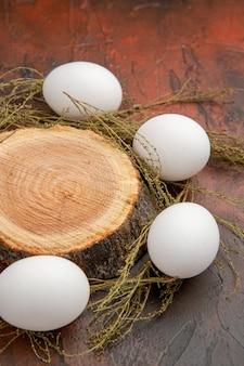 Uova di gallina bianche vista frontale sulla superficie scura