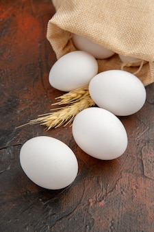 Front view white chicken eggs on the dark surface