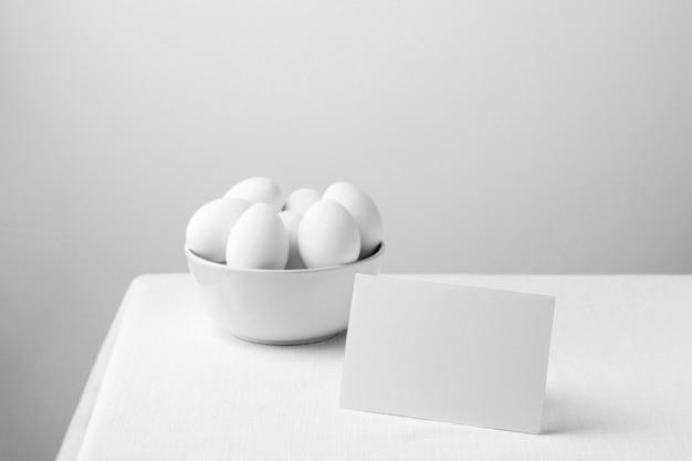 空白のメモとボウルの正面図白い鶏の卵