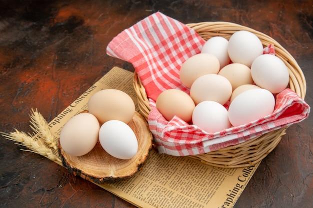Uova di gallina bianca vista frontale all'interno del cesto su superficie scura