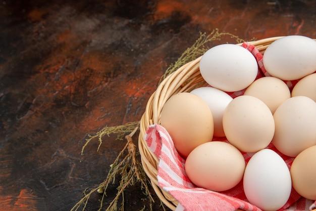 Uova di gallina bianca vista frontale all'interno del cesto con asciugamano sulla superficie scura dark
