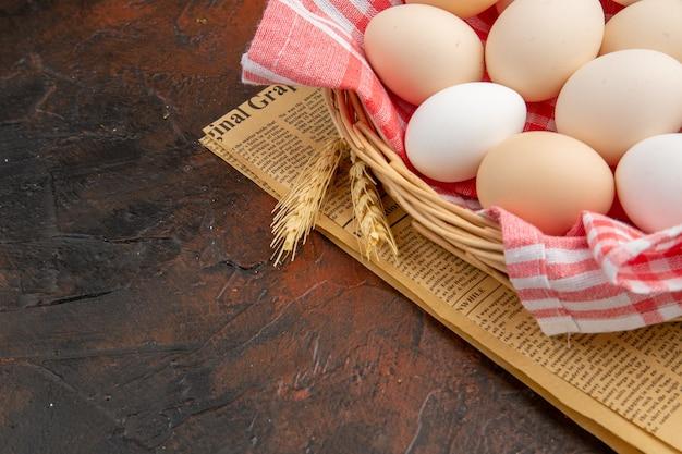 어두운 표면에 수건으로 바구니 안에 전면보기 흰색 닭고기 달걀