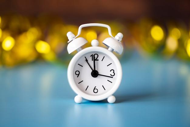 Вид спереди белые часы на размытом золотом фоне