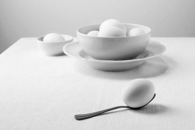 Вид спереди белые яйца в миске