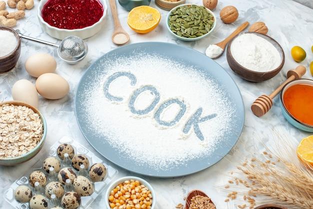 正面図白い背景にナッツの種と卵が入ったプレート内の白い小麦粉ナッツ生地焼き食品カラーケーキビスケットパイクック写真
