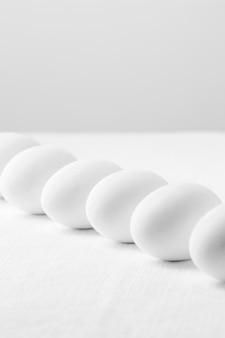 Вид спереди белые свежие яйца на столе