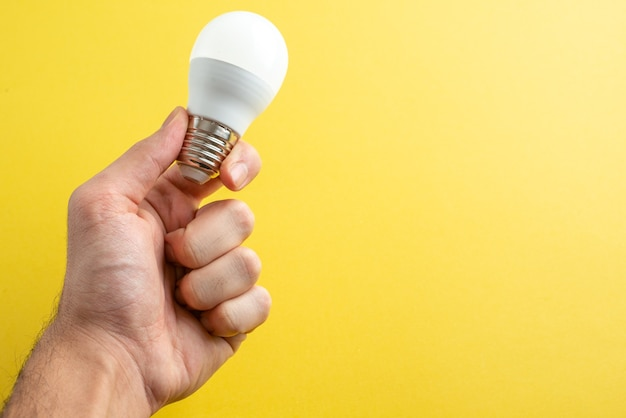Lampadina bianca vista frontale sulle mani maschio su sfondo giallo colore luce foto elettricità casa camera umana