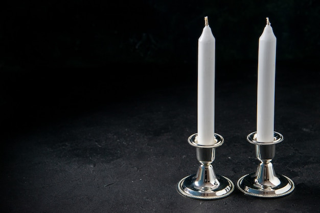 Front view of white long candles on dark floor war evil death funeral light