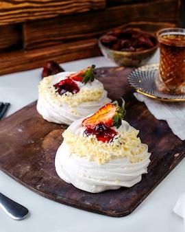 Вид спереди белых зефиров вместе с нарезанной красной клубникой на коричневом деревянном столе
