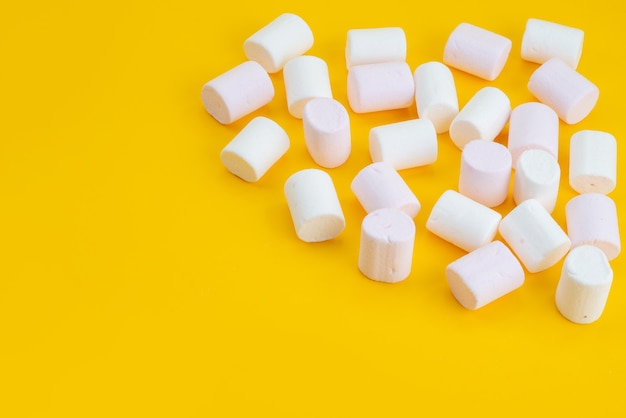 A front view white marshmallows delicious goodies on yellow desk, sugar sweet candy color