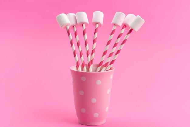 Un marshmallow bianco vista frontale con bastoncini rosa all'interno della tazza rosa sul rosa