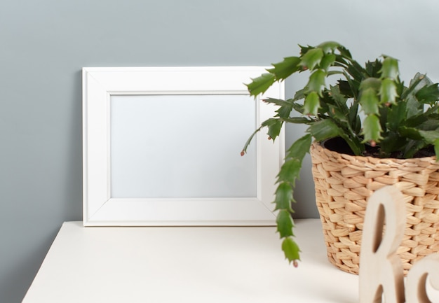 Front view of white poster frame mockup with  plant in a pot over the grey wall