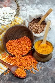 明るい表面にオレンジ色のレンズ豆とコショウと正面図の白い種子