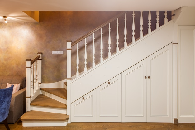 Front view of white staircase to the second floor with built-in lockers made of wood. classic style interior of a guest room in a two-level apartment.