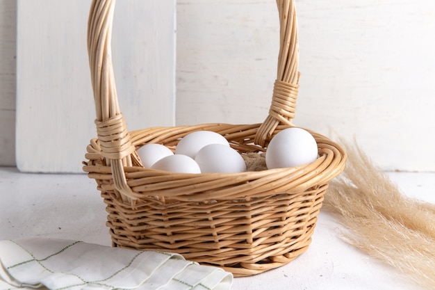 Вид спереди белые целые яйца внутри корзины на белом столе.