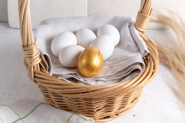 Front view white whole eggs inside basket with golden one on the white desk.