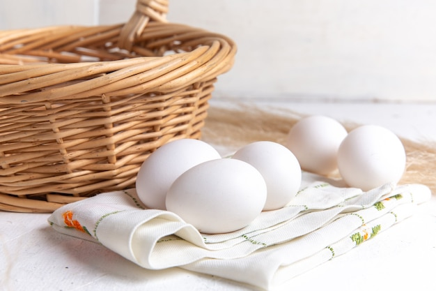 Front view white whole eggs with basket on the white background.