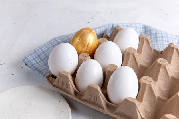 Vista frontale uova intere bianche con quella dorata su sfondo bianco.