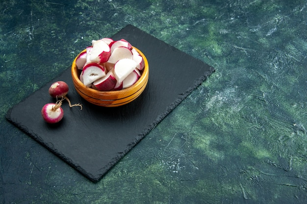 Front view of whole and chopped fresh radishes in bowl on the right side on dark color cutting board on green black mixed colors background with free space
