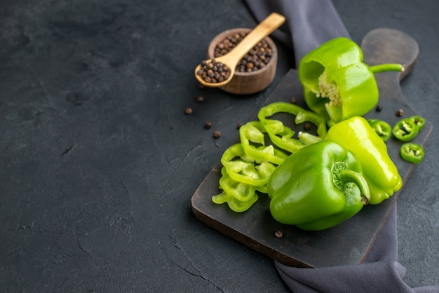 Front view of whole cut chopped green peppers on wooden cutting board on dark color towel on black surface