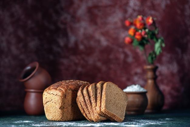 Vista frontale del pane nero dietetico intero tagliato e ciotole vaso di fiori su sfondo blu marrone colori