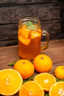 Vista frontale di arance fresche intere e tagliate con foglie e succo naturale in un bicchiere su sfondo marrone