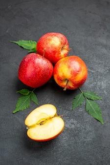 Vista frontale di mele e foglie rosse fresche intere e tagliate su sfondo nero