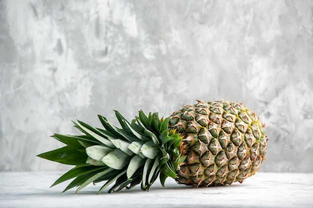 Front view of whole fresh falling golden pineapple on ice wall with free space