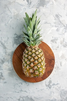 Vista frontale dell'intero ananas dorato fresco sul tagliere sulla superficie di marmo