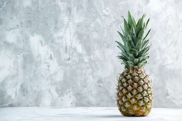 Front view of whole fresh golden pineapple on the left side standing on marble surface